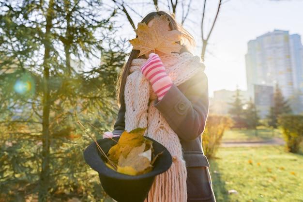 Ritratto all'aperto di autunno della ragazza con le foglie di acero gialle