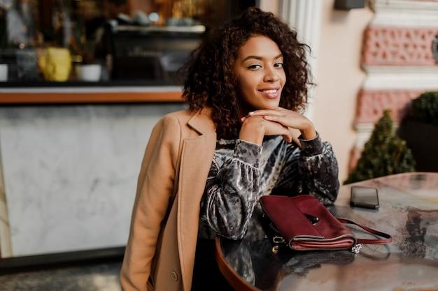 Ritratto all'aperto di bella donna di colore sorridente con i capelli afro alla moda che si siedono in caffè a parigi.