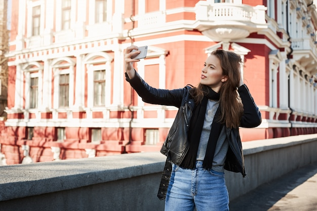 Ritratto all'aperto di bella donna in piedi nel centro della città, in posa tenendo smartphone e prendendo selfie, indossando abiti alla moda
