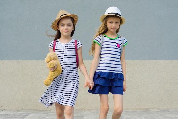 Ritratto all'aperto di due amici 7, tenendosi per mano di 8 anni.