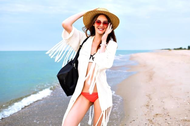 Ritratto all'aperto di estate della donna abbastanza bionda che indossa bikini, giacca stile boho e occhiali da sole, in posa vicino all'oceano, buon umore di vacanza di viaggio