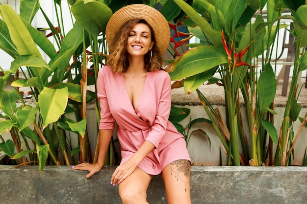 Ritratto all'aperto di estate della donna castana seducente con i capelli ondulati nella posa rosa del vestito