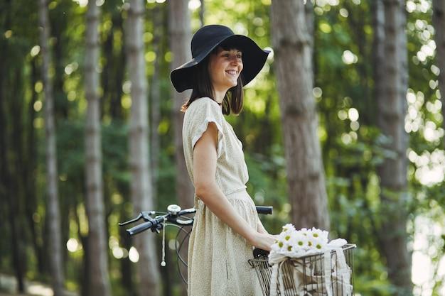 Ritratto all'aperto di giovane castana attraente in un cappello su una bicicletta.