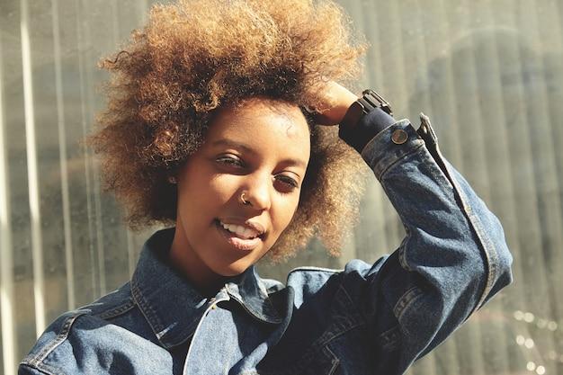 Ritratto all'aperto di giovane donna dalla carnagione scura alla moda con capelli ricci che indossa giacca di jeans
