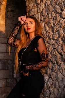 Ritratto all'aperto di modo di giovane bella donna caucasica che posa sulla luce del tramonto.