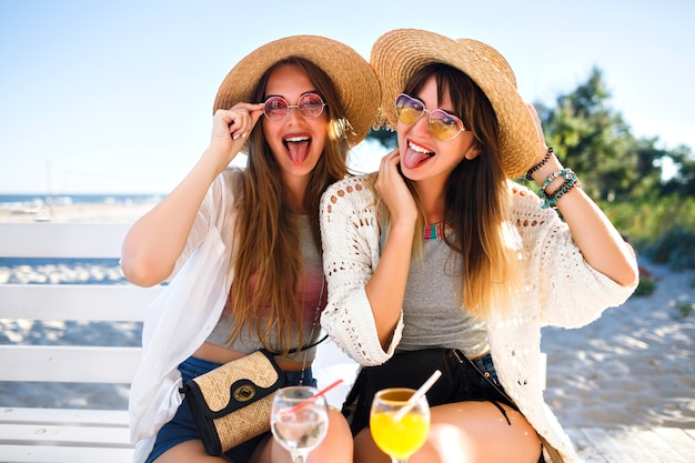 Ritratto all'aperto di ragazze hipster divertenti e felici della compagnia che impazziscono sul caffè sulla spiaggia, bevendo gustosi cocktail ridendo e sorridendo, abiti estivi vintage boho luminosi, relazioni e divertimento.