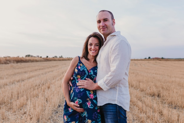 Ritratto all'aperto di una giovane coppia incinta in un campo giallo. all'aperto stile di vita familiare.