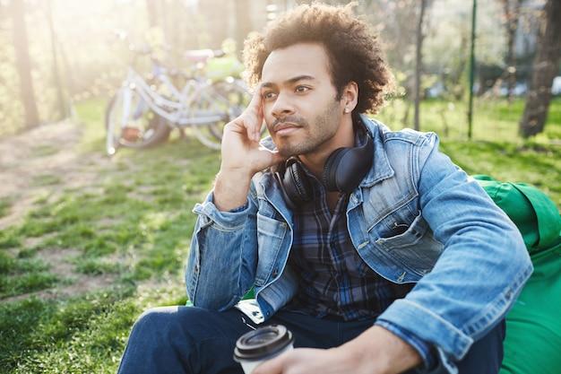 Ritratto all'aperto di uomo africano alla moda seduto nel parco con una tazza di caffè, tenendo la mano sul viso e guardando da parte mentre si pensa o si sogna
