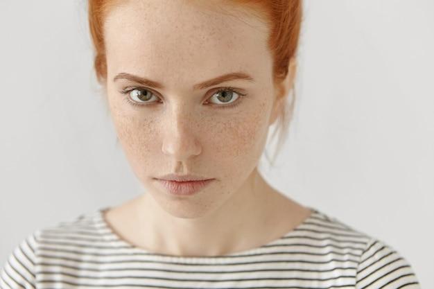 Ritratto altamente dettagliato del primo piano del modello femminile della giovane rossa stupefacente con gli occhi verdi