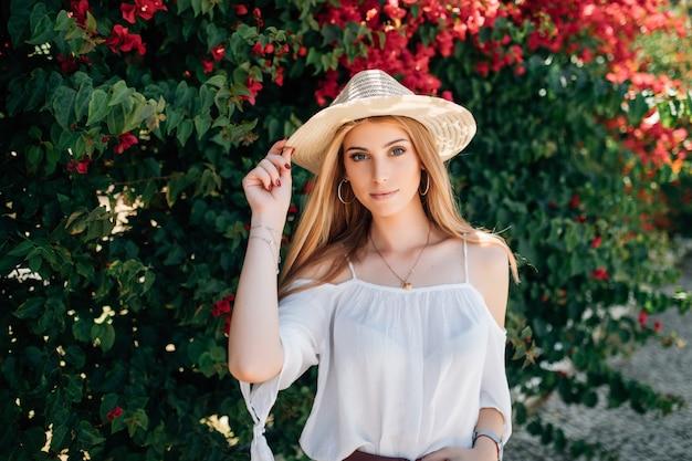 Ritratto alto vicino all'aperto di giovane bella ragazza riccia sorridente felice che porta cappello di paglia alla moda in strada vicino a rose in fiore. concetto di moda estiva. copia spazio