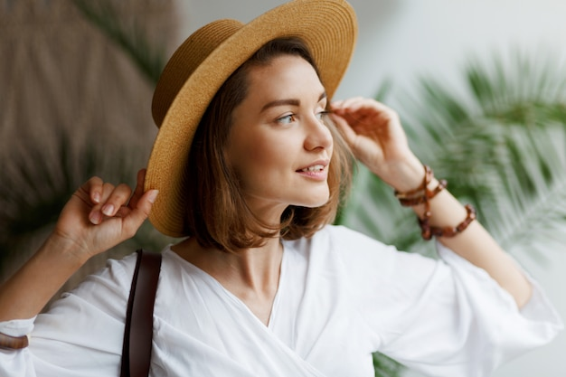 Ritratto alto vicino dell'interno della donna graziosa elegante in cappello di paglia e blusa bianca che posano a casa