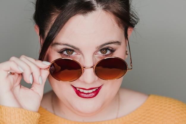 Ritratto alto vicino della giovane donna con sorridere degli occhiali da sole. ha portato l'anello riflesso negli occhi. concetto di donna vera