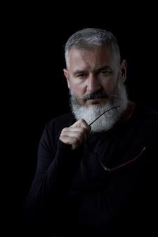 Ritratto artistico di un uomo dai capelli grigio brutale con una barba e vetri su un fondo nero, fuoco selettivo