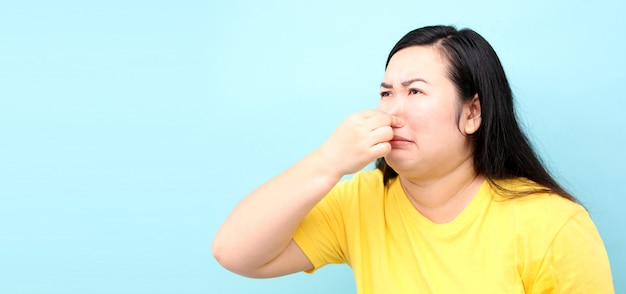 Ritratto asia donna sente fallo, su sfondo blu in studio