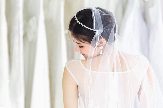 Ritratto asiatico di signora carina sorridente felice indossando abito da sposa