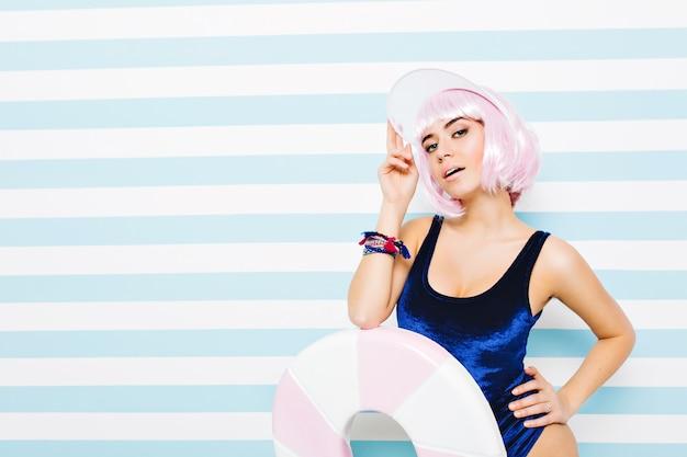 Ritratto attraente incredibile giovane donna in tuta blu rilassante sulla parete a strisce bianco-blu. indossare acconciatura rosa tagliata, berretto da spiaggia, grande lecca-lecca. modello sexy, umore allegro.