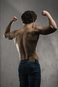 Ritratto attraente sexy narcisista torso nudo ragazzo dimostrando il suo bicipite in palestra