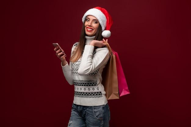 Ritratto beautifiul caucasica donna cappello santa sulla parete rossa. concetto di natale capodanno. emozioni positive sorridenti dei denti svegli della donna con il sacchetto della spesa e l'acquisto online del telefono