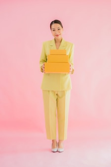 Ritratto bella giovane donna asiatica con cassetta dei pacchi sul colore