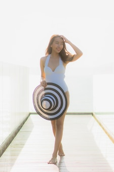 Ritratto bella giovane donna asiatica felice e sorriso sulla spiaggia mare e oceano