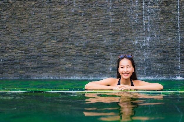 Ritratto bella giovane donna asiatica in piscina nei dintorni di hotel e resort