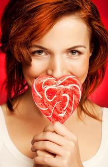 Ritratto bella giovane ragazza bionda sexy con cuore lecca-lecca rosso