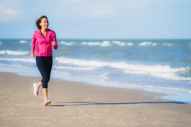 Ritratto bello giovane funzionamento asiatico della donna o esercizio sul paesaggio della natura del tropica della spiaggia