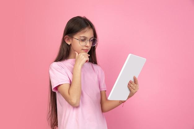 Ritratto caucasico della bambina sulla parete rosa