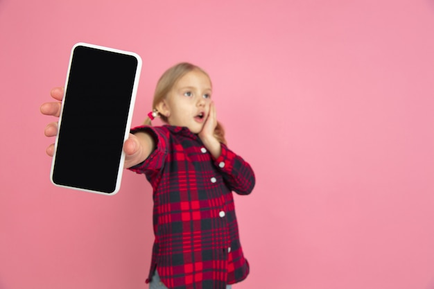 Ritratto caucasico della bambina sullo studio rosa