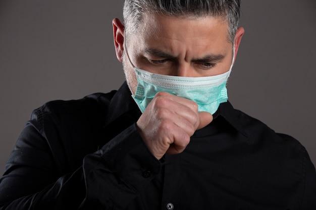 Ritratto chiuso dell'uomo con la maschera chirurgica che tossisce nello studio su fondo grigio, concetto di sanità.