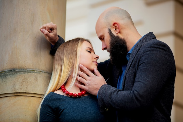 Ritratto closeup coppia di capelli lunghi giovane sensuale donna indietro arcuata toccando la barba dell'uomo con i baffi chinati sul viso della ragazza tenendo i capelli, foto verticale