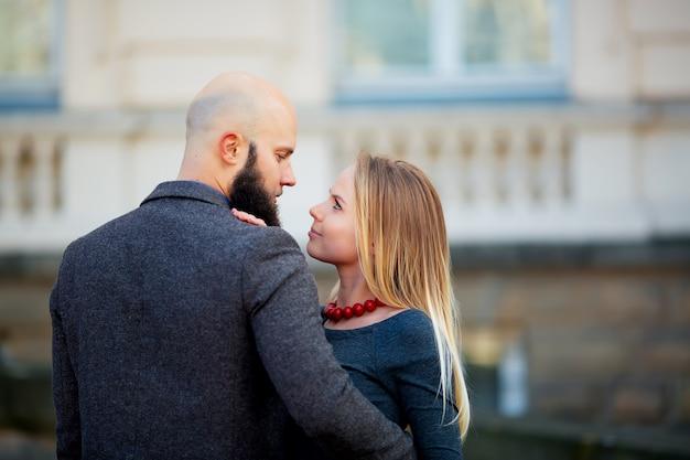 Ritratto closeup coppia di capelli lunghi giovane sensuale donna indietro arcuata toccando la barba dell'uomo con i baffi chinati sul viso della ragazza tenendo i capelli grigi, foto verticale