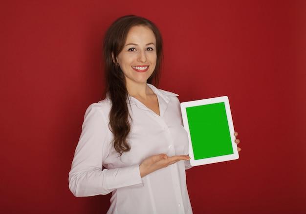 Ritratto con spazio di copia posto vuoto della donna alla moda sicura abbastanza affascinante in camicia classica con tablet nelle mani isolato su rosso