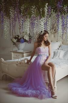 Ritratto creativo di una donna di moda con fiori in splendido abito romantico rosa lungo