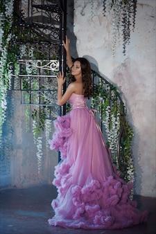 Ritratto creativo di una donna di moda in splendido abito romantico rosa lungo