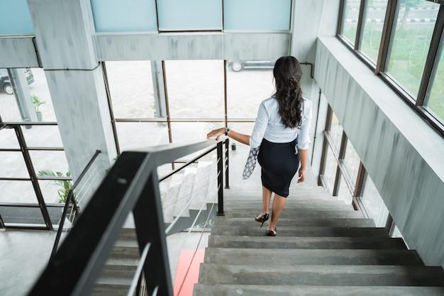 Ritratto da dietro della donna di affari che cammina da solo le scale