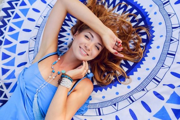 Ritratto dall'alto di una donna graziosa che si distende sul telo da spiaggia nella soleggiata giornata estiva. braccialetti e collana alla moda boho.