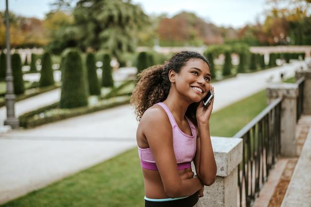Ritratto degli abiti sportivi d'uso sorridenti della giovane donna che parlano sul telefono all'aperto.