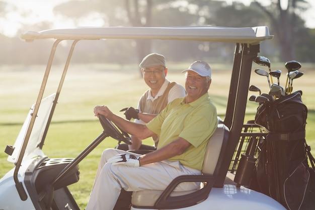 Ritratto degli amici allegri del giocatore di golf che si siedono in carrozzino di golf