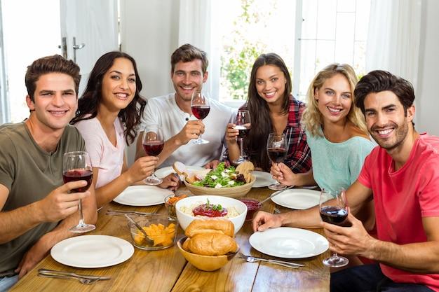 Ritratto degli amici felici che tengono i vetri di vino mentre pranzando