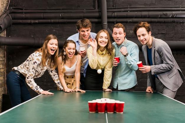 Ritratto degli amici maschii e femminili che giocano il pong della birra sul tavolo