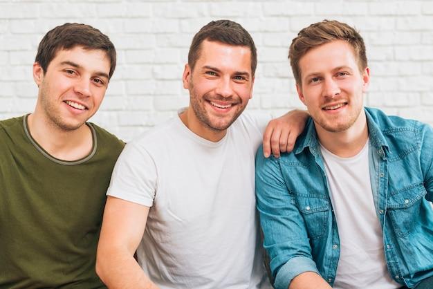 Ritratto degli amici maschii sorridenti che esaminano macchina fotografica contro il muro di mattoni bianco