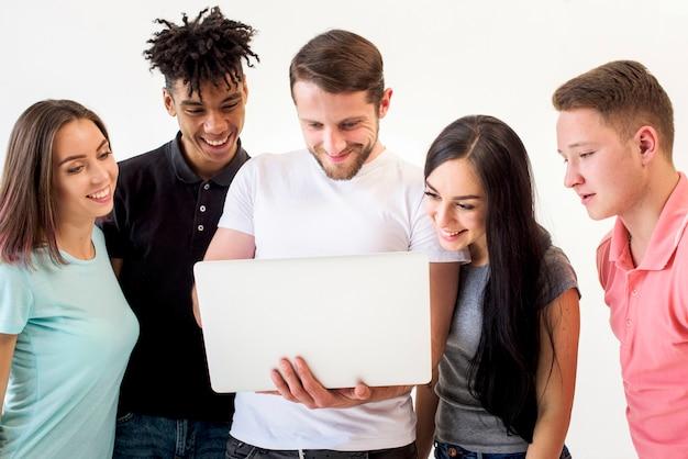 Ritratto degli amici multietnici che considerano il computer portatile che si leva in piedi nella priorità bassa bianca
