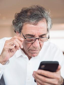 Ritratto degli occhiali d'uso dell'uomo senior che esaminano telefono cellulare