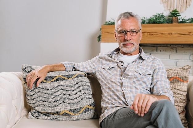 Ritratto degli occhiali d'uso dell'uomo senior che si siedono sul sofà