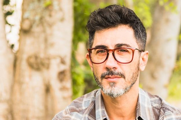 Ritratto degli occhiali d'uso di un uomo che esaminano macchina fotografica