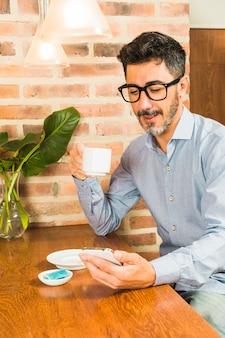 Ritratto degli occhiali d'uso di un uomo che tengono la tazza di caffè che esamina smartphone