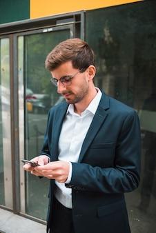 Ritratto degli occhiali d'uso di un uomo d'affari facendo uso del telefono cellulare