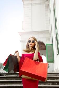 Ritratto degli occhiali da sole d'uso della donna asiatica con i sacchetti della spesa