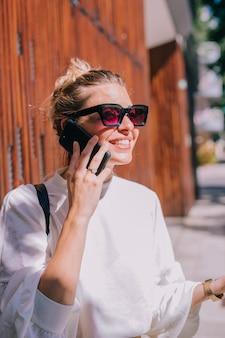 Ritratto degli occhiali da sole d'uso sorridenti della giovane donna che parlano sul cellulare